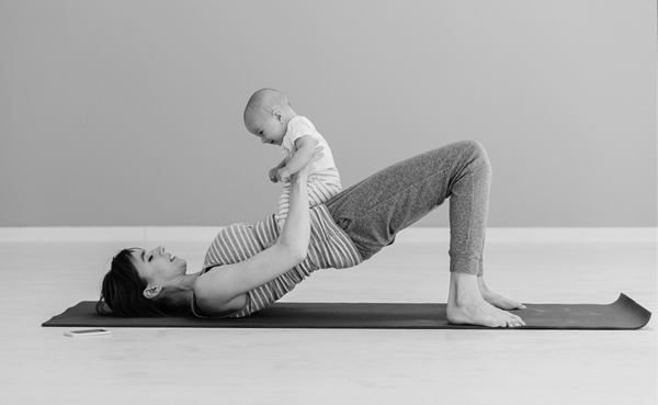 A mum working out holding her baby