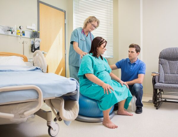 Nurse and husband helping the pregnant woman