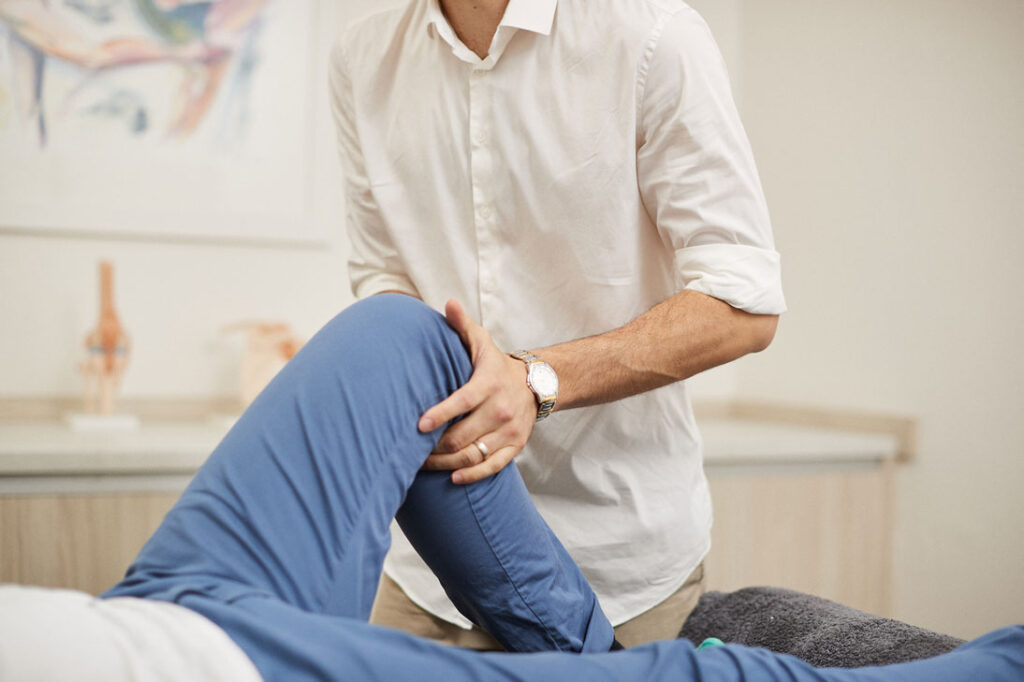 Physiotherapist checking leg of the patient
